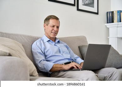 Smiling happy middle aged 50s old senior man using laptop computer technology working online, surfing internet, typing email, shopping in ecommerce store relaxing with device sitting on couch at home.