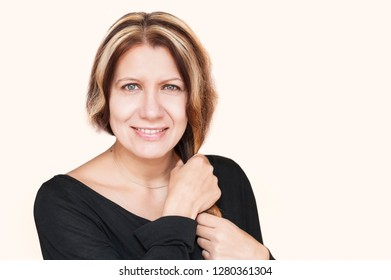 A smiling happy middle-aged woman on a light background holds her beautiful hair with her hands and is glad that it is not gray because she painted it. Beauty concept. Copy space