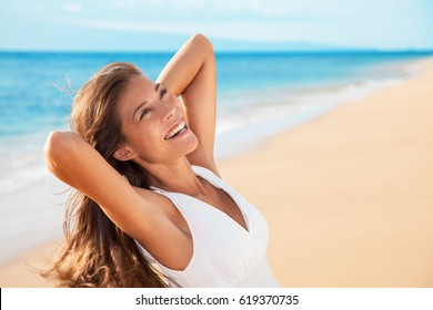 Smiling happy mixed race woman enjoying serene sunset. Carefree Asian woman relaxing on beach travel holidays vacation. Freedom and wellness concept.