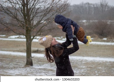 smiling happy mother is looking with love at her beautiful adorable little baby son holding up above her head with nature covered with snow in the background