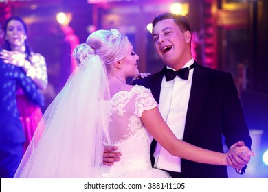 Smiling happy newlyweds dancing in the restaurant hall