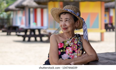 Smiling happy old woman leaning on a table enjoying an outdoor tropical view.