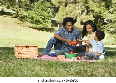Smiling happy parents and son having picnic in park.