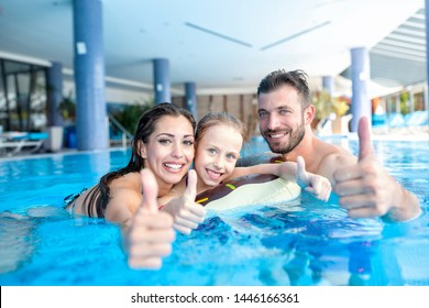 Smiling happy people in the swimming pool, family concept