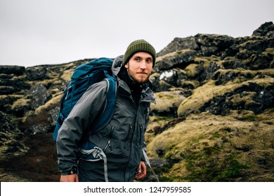 Smiling and happy portrait of young handsome traveller or hiker enjoying the outdoors activity. Wears winter jacket and beanie, together with backpack for tent and gear. Nomad lifestyle