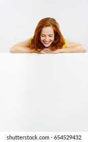 Smiling happy pretty young redhead woman looking down at a blank white sign with copy space as she leans her arms along the top
