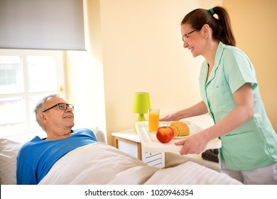 Smiling happy senior patient waiting breakfast at nursing home