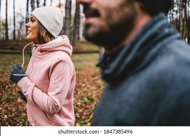 Smiling happy sportswoman with beanie and gloves running with her friend in woods at autumn. Healthy lifestyle.