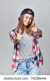 Smiling happy teen girl pointing at camera with both hands, over grey background
