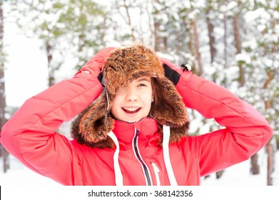 Smiling happy teenage girl in warm earflap having fun in winter forest. Multicolored vibrant outdoors horizontal image.