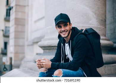 Smiling happy teenager or young male student sits on top of stairs in front of university or highschool, wears black hoodie and cap, smiles at camera, successful and handsome