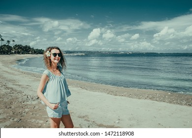 Smiling happy tourist woman enjoy vacation on Kuta beach. Bali traveller. Explore beautiful Indonesia landscape. People travel. Tourism concept. Tropical resort. Copy space. Blue sky background