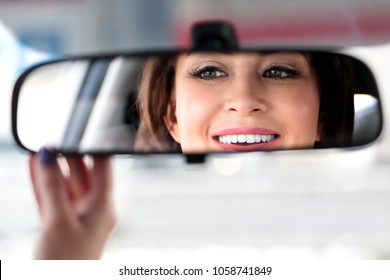 Smiling happy woman car driver is adjusting the rear view mirror with her hand.