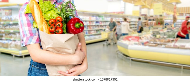 Smiling happy woman enjoying shopping at the supermarket, holding vegetables in eco friendly bag