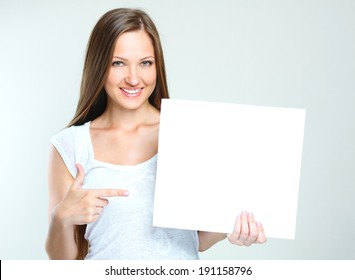smiling happy woman holding  blank paper. empty copyspace for ads.