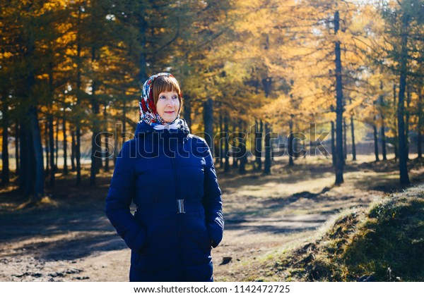 smiling happy woman of retirement age in autumn coat, yellow leaves
