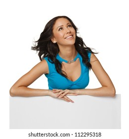 Smiling happy woman standing behind and leaning on a white blank billboard / placard, looking to the side, over white background