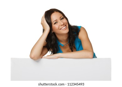 Smiling happy woman standing behind and leaning on a white blank billboard / placard, over white background