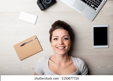 Smiling happy woman surrounded by office supplies with a camera, notebook, laptop and tablet computer as she lies on the floor in a close up on her face