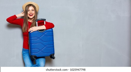 Smiling happy woman with travel suitcase. Gray wall back.
