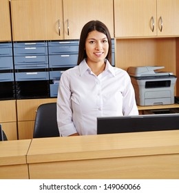 Smiling happy woman workingt at reception in a hospital