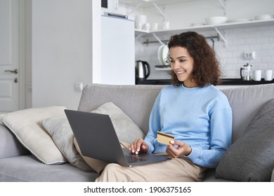 Smiling happy young 20s woman customer, shopper, consumer making online purchase holding credit card using laptop computer at home. Fashion ecommerce shopping and secure internet payments concept.
