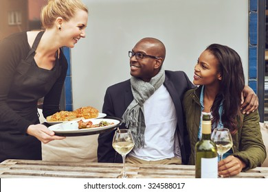 Smiling happy young Caucasian waitress serving a loving African American couple dinner as they sit arm in arm at a table in a restaurant