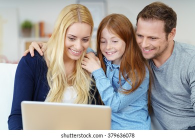 Smiling happy young family enjoying surfing the internet on a laptop computer as they relax together at home on a sofa
