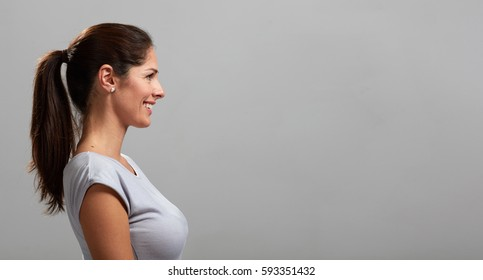 Smiling happy young girl over gray wall background