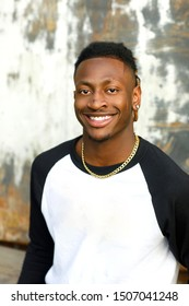 smiling happy young Handsome African American Black Male outside wearing a black and white baseball jersey henley shirt