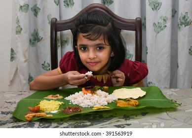 Smiling/ happy young Indian girl / child / kids wearing traditional dress eating  Onam sadhya with hand for festival, Kerala India. Asian child. Beautiful daughter in traditional Indian sari on Vishu