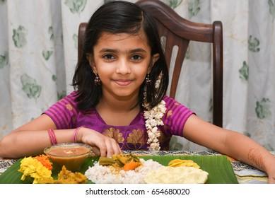 Smiling / happy young Indian girl / kid / child / female wearing traditional dress eating Onam sadhya with hand for festival, Kerala India. Asian child. Beautiful daughter Indian sari on Vishu, diwali