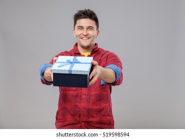 Smiling happy young man presenting a gift isolated on gray