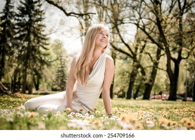 Smiling happy young person (teenager) sitting outdoors in blooming grass and looking away