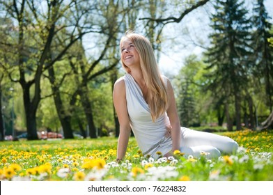 Smiling happy young person (teenager) sitting outdoors in blooming grassfiled and looking away