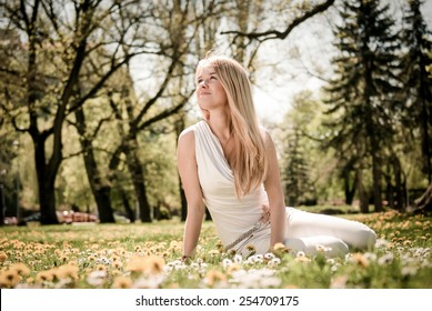 Smiling happy young terson (teen girl) sitting outdoors looking away
