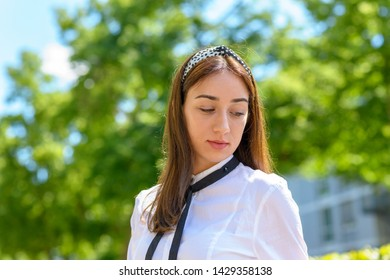 Smiling happy young woman with long brown hair wearing a headband and looking down outdoors in the sunshine