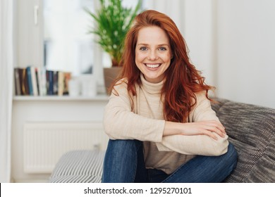 Smiling happy young woman with a vivacious smile sitting with her feet up relaxing on a sofa at home