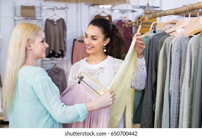 Smiling happy young women shopping at the clothing store