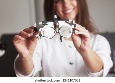 Smiling and have good mood. Female doctor showing the little phoropter by holding it in two hands.