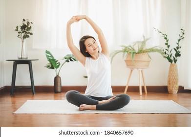 Lächelnde gesunde Asiatin, die Yoga-Schulter zu Hause im Wohnzimmer