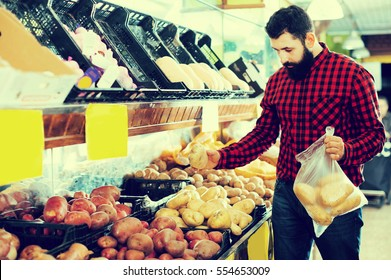 Smiling healthy man seller showing potatoes in grocery shop