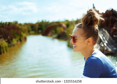 smiling healthy solo traveller woman in blue t-shirt on river boat exploring countryside while having river cruise.