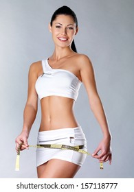 Smiling healthy woman after dieting measures hip. Healthy lifestyle.