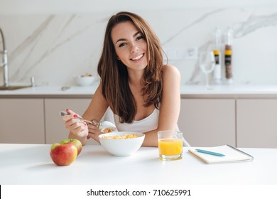 Smiling healthy woman eating corn flakes cereal while sitting and having breakfast at the kitchen table