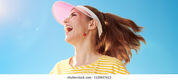 smiling healthy woman in yellow shirt against blue sky looking aside