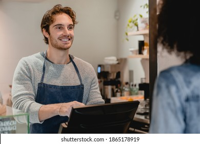 Smiling helpful young waiter servicing the customer at cash point in cafe