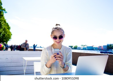 Smiling hipster girl in fashionable glasses skilled blogger posting article in social network via mobile phone during online learning via laptop computer, sitting outdoors near embankment river