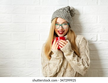 Smiling Hipster Girl in Knitted Sweater and Beanie Hat with Mug in Hands at White Brick Wall Background. Winter Warming Up Concept.