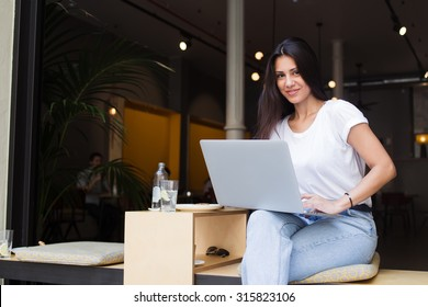 Smiling hipster girl looking at the camera while working on laptop computer in modern coffee shop in the fresh air, charming latin woman using net-book for distance work while sitting in sidewalk cafe